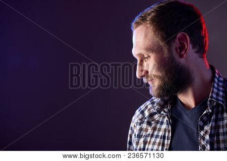 Profile Closeup Portrait Of Bearded Man Looking Down Over Dark Background, Red And Blue Backlit