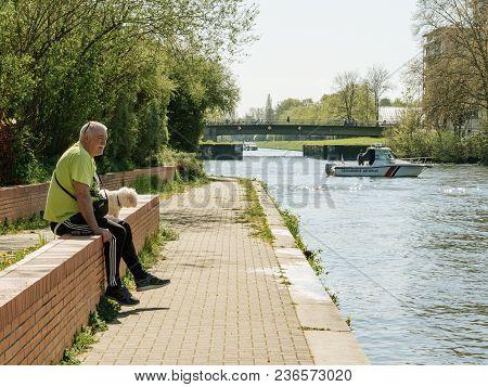Strasbourg, France - Apr 17, 2018: Senior Man With Dog Looking At National Gendarmerie Boat Near Eur