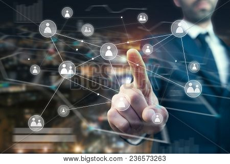 Businessman With Hand Holding Virtual Social Media Buttons In City Background