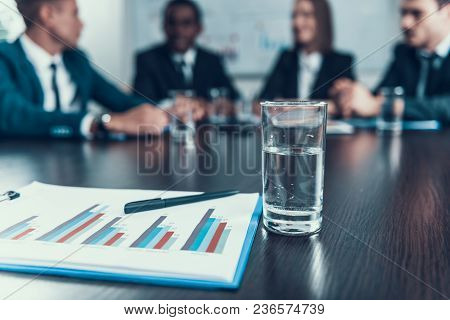 Close Up. Glass With Water And Image Of Charts Lie On Table, Behind Which Business Meeting Is Held.