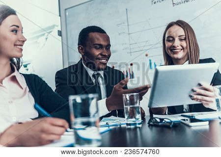 Success Smiling Woman Shows Something On Computer Tablet To Black Businessman At Business Meeting. B