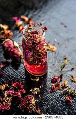 Close up of extracted rose water or gulab jal or gulab ka pani in a transparent bottle on black surface used in many holy works. poster