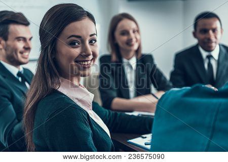 Young Successful Woman Is Sitting At Business Meeting With Colleagues In Conference Room. Business M