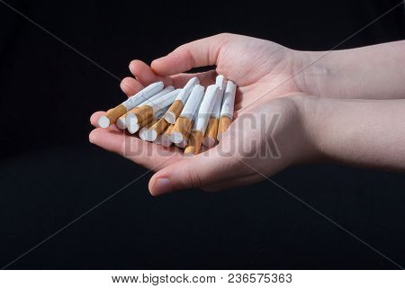 Hand Is Giving Out Bundle Of Cigarettes On Black Background