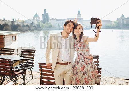 Outdoor Shot Of Happy Woman And Man Embrace Each Other And Pose For Making Selfie, Have Stroll Near