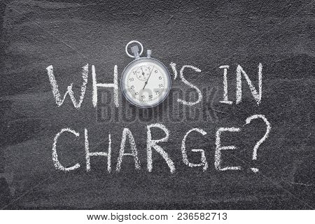 Who Is In Charge Question Handwritten On Chalkboard With Vintage Precise Stopwatch Used Instead Of O