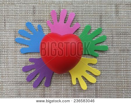 Red heart on colorful palm print