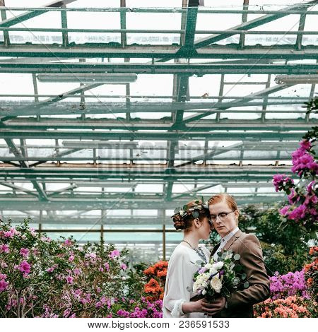 Romantic Bride And Groom Hugging Each Other In Greenhouse
