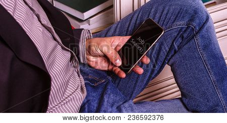 A Smartphone With The Inscription Job Search In The Hands Of A Man Dressed In Blue Jeans And A Busin
