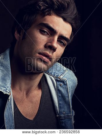 Sexy Serious Male Model Posing In Blue Jacket On Dark Shadow Background. Fashion Style Toned Color C