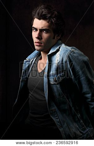 Thinking Serious Charismatic Man In Blue Jeans Looking On Dark Shadow Dramatic Light Background. Clo