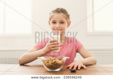 Happy Child Girl Drinking Milk In Glass While Sitting At Kitchen Table. Kid, Healthy Food, Nutrition