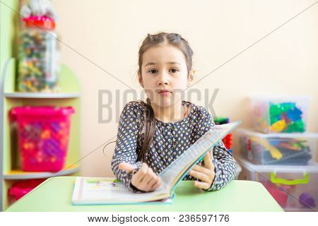 Cute Little Girl Doing Homework, Reading A Book, Coloring Pages, Writing And Painting. Children Pain