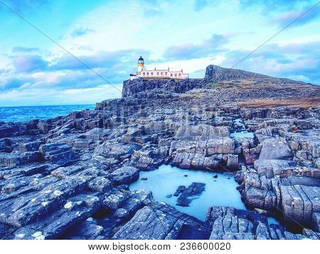 Old Lighthouse On The End Of Thin Spit Of Land. Sharp Rocky Cliff Aganst To Foamy Ocean, Evening Blu