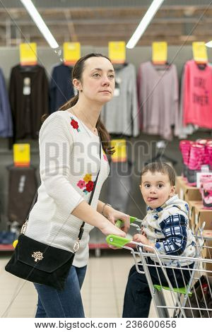Mom With A Child In A Trolley In A Shopping Center. Mom With A Small Son In A Shopping Center. Mom D