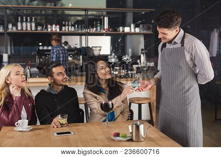 Smiling Waiter Taking Credit Card From Customer To Pay For Beverage At Coffee Shop Counter. Small Bu
