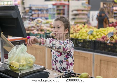 A Girl At A Supermarket Weighing Apples. The Concept Of Adult Children.