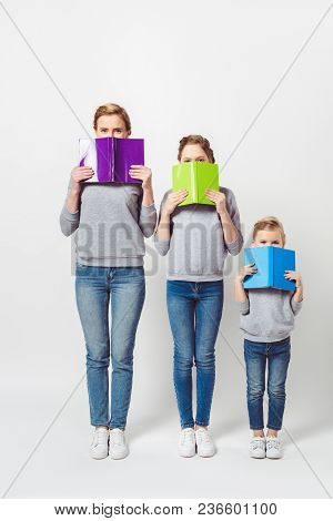 Obscured View Of Mother And Daughters In Similar Clothing Covering Faces With Books Isolated On Grey
