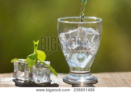 A Glass With Ice Cubes Pour Soda Water From A Bottle, Nearby Lie Ice Cubes And Mint, In The Open Spa
