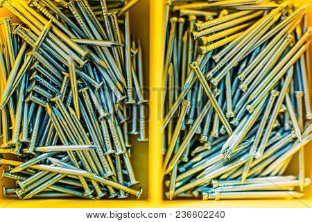 Top View Many New Screw Nails In Yellow Container Box