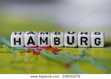 Word Hamburg Formed By Alphabet Blocks On Atlas Map Geography
