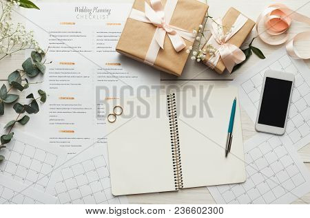 Wedding Background With Checklist. Paper Planner And Wedding Rings On White Wooden Table With Lots O
