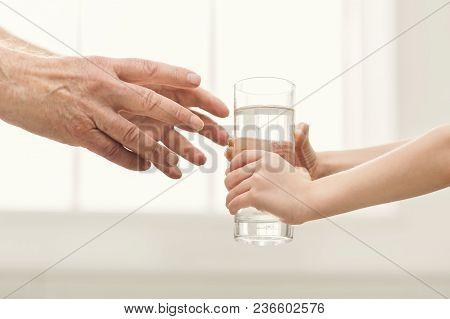 Kid Hand Giving Glass Of Water To Grandfather, Closeup. Love, Care And Respect For Elder Generation,