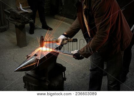 Spark. Dark Background.the Blacksmith Manually Forging The Molten Metal On The Anvil In Smithy With