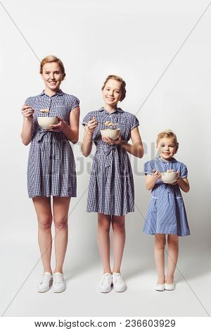 Mother And Daughters In Similar Dresses With Cereal Breakfast In Bowls On White