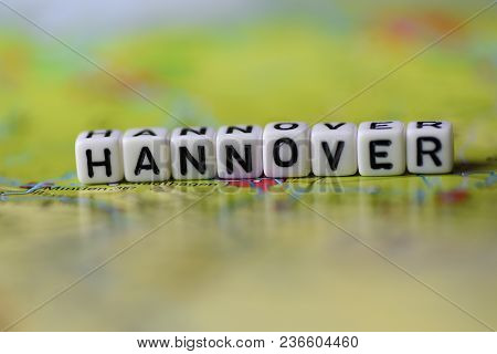 Word Hannover Formed By Alphabet Blocks On Atlas Map Geography