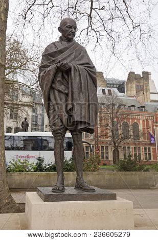 Parliament Square, London, Uk, 2018.  Mahatma Gandi Memorial Statue Stands On A Tree Lined Road And