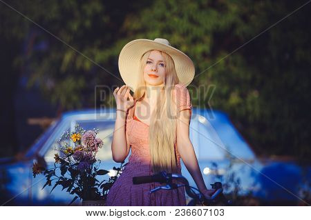 Beautiful Girl Wearing A Nice Dress Having Fun In A Country House With A Bicycle, Holding A Beautifu
