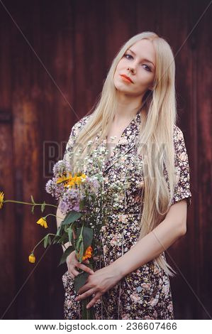 Beautiful Young Woman In Doted Summer Dress On Red Old Wooden Background, Looking At Camera. Rustic
