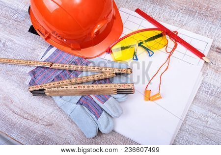 Orange Hard Hat, Earplug, Safety Glasses And Gloves For Work. Earplug To Reduce Noise On A White Bac