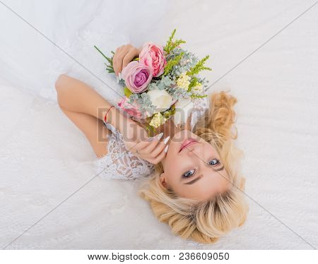 Young beauty fashion bride on bed decor with bouquet of flowers in her hands. Beautiful Bride portrait wedding makeup and hairstyle. Fashion bride model in luxury wedding dress. Beauty girl face, gorgeous beauty bride.