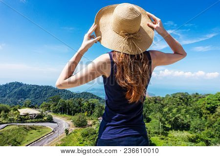 Young Traveling Woman Wearing Hat And Standing On The Top Of The Mountain Cliff With Relaxing Mood A