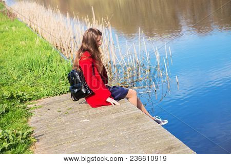 Lonely Young Teenage Girl Sitting On The River Bank. Youth, Sadness, Loneliness, Reflections Concept