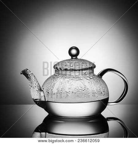 Glass Teapot With Boiling Water And Drops Of Condensation On Glass Advertising Shot On Light Black A