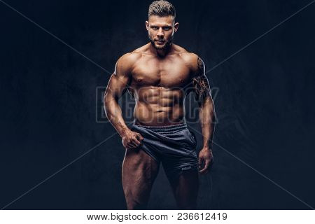 Portrait Of A Handsome Shirtless Tattooed Bodybuilder With Stylish Haircut And Beard, Shows A Muscle
