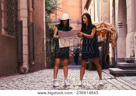 Two Female Tourists Are Standing In The Middle Of A Narrow Street, And Look For Sights On The Map.