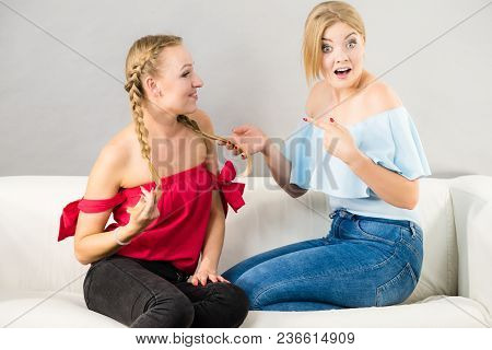 Pretty Blonde Shocked Woman Pointing At Her Female Best Friend Braided Hair
