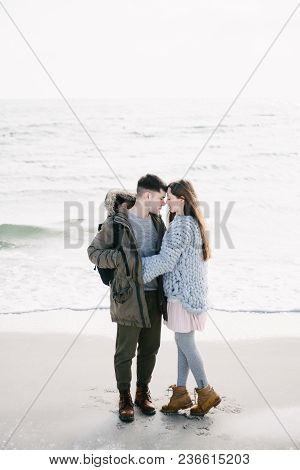 View Of Young Couple Embracing On Winter Seashore