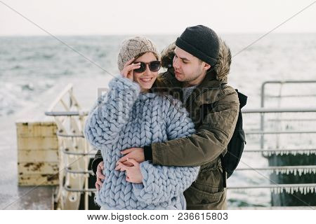 Boyfriend Embracing His Smiling Girlfriend In Merino Sweater On Winter Quay