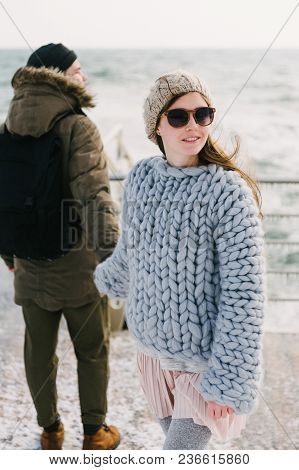 Stylish Girl In Merino Wool Sweater Holding Hands With Boyfriend On Winter Quay At The Sea