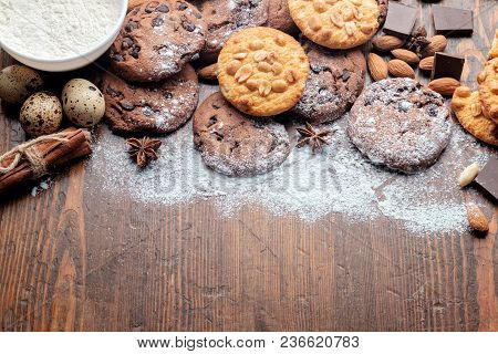 Chocolate Chips Cookies, Peanut Cookies And Scattered Nuts On Old Dark Rustic Texture With Copy Spac