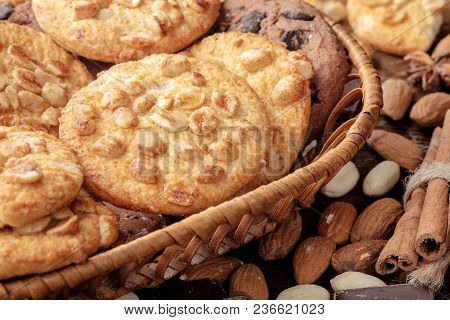 Peanut Cookies And Chocolate Chips Cookies In Wicker Basket And Scattered Nuts Near It. Close-up Vie