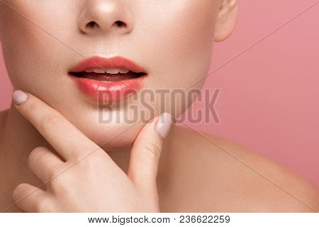 Close Up Of Female Lips Painted With Natural Tone Gloss. Woman Touching Chin With Two Fingers. Isola