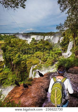 Scenic basaltic rock formations famous waterfalls Iguazu Falls. Energetic woman with a tourist backpack watching waterfalls. Concept of active and extreme tourism