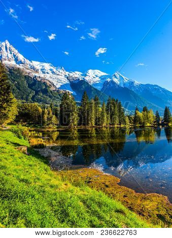 Chamonix City Park is illuminated by sunset. The lake reflects the mountains, the forest and the blue sky. Sunny autumn day in the French Alps. Concept of active winter tourism