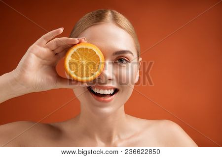 Portrait Of Pleased Woman With Rich Pelt Covering One Eye With Half Of Orange. Copy Space In Right S